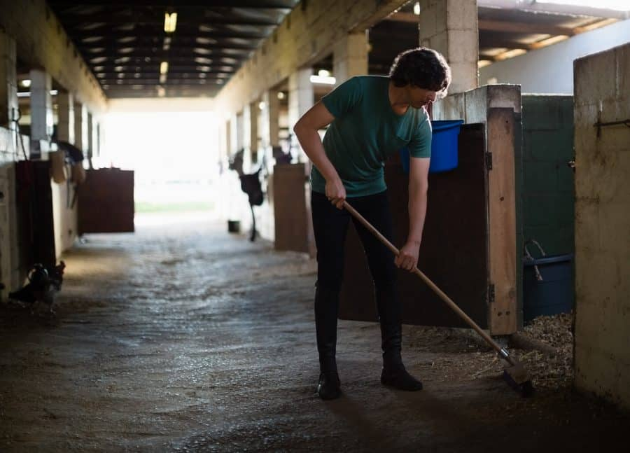 Man sweeping stable